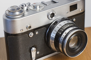 Old rangefinder film camera lying on the wooden surface