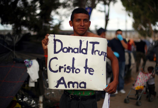 """A migrant, part of a caravan of thousands from Central America trying to reach the United States, holds a sign saying """"Donald Trump Christ loves you"""" as he walks through a temporary shelter in Tijuana"""