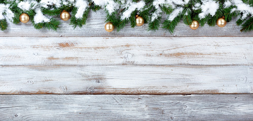 Snowy Christmas evergreen branches and golden ornaments on white vintage wooden planks
