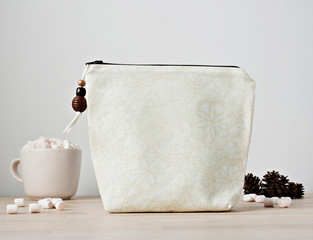 Beige boho girl makeup bag with wooden beads, cup with marshmallows and pine cones on the desk