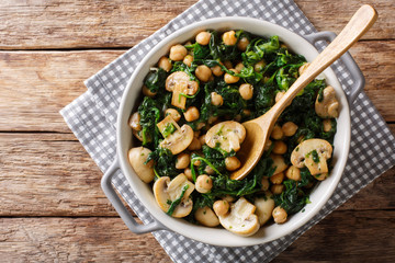 Stew of chickpeas with spinach and mushrooms close-up in a bowl. horizontal top view