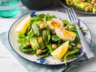 Avocado spinach salad with chickpeas and hard boiled eggs served on a dish. Fats and proteins
