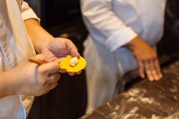 Chef making circle shape Ravioli by filling sage and butter on pasta dough.