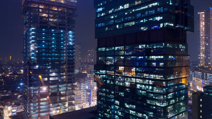 Two skyscrapers with glowing light at night Wall mural