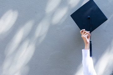 Graduation concept. She is holding Graduation cap. to celebrate in success.