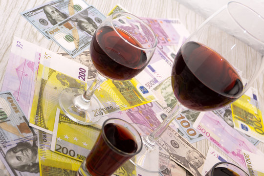 Glass of red wine and money on an old wooden table. Angle view, focus on the glass of red wine .