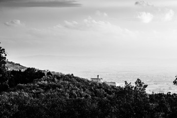 Beautiful view of Assisi town (Umbria) in autumn from an unusual place, behind an hill with trees