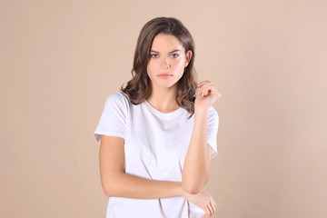 Cheerful brunette woman dressed in basic clothing looking at camera, isolated on beige background.