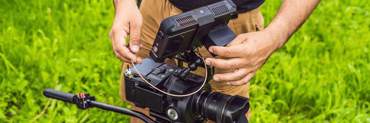 a professional cameraman prepares a camera and a tripod before shooting BANNER, long format