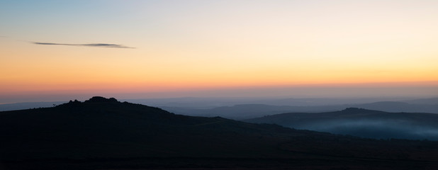 Stunning sunset silhouette landscape image of Foggintor in Dartmoor