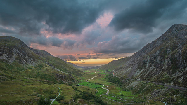 Beautiful dramatic landscape image of Nant Francon valley in Snowdonia during sunset in Autumn