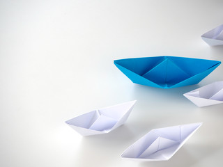 Blue paper boat leading among white ships