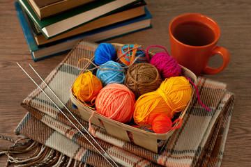 Knitting in a cozy atmosphere. A basket of yarn for knitting, a cup of tea, a book, a checkered scarf create coziness. Knitting clothes from colorful yarn.