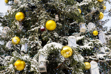 Decorated Christmas tree covered with snow. Natural christmas tree with yellow balls, gift boxes and toys. Snowy and happy Wintertime