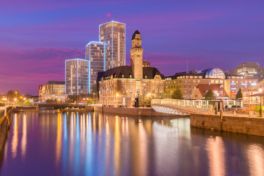 Evening cityscape of Malmo, Sweden. Modern and old historical buildings reflected in the water. Picturesque sunset in a city