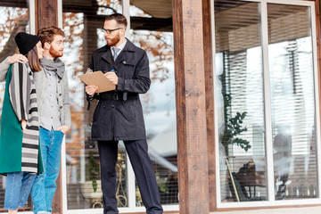 Young caucasian couple in autumn wear standing on the house porch with real estate agent, ready to make a deal , purchase or rent concept.