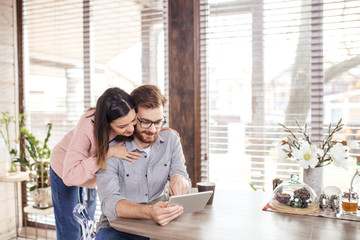 Loving young european couple hugging and using tablet on the kitchen, surfing the net together.