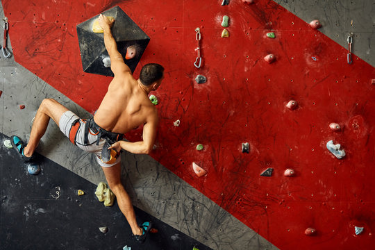 Panoramic shot of young muscular man training in indoor clymbing gym. Rear view of sportsman climber moving up on steep rock, climbing on artificial wall. Extreme sports and bouldering concept.