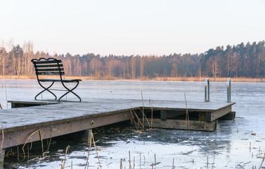 Einsamer Holzsteg am zugefrorenem See im Winter