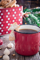 Red tea mug with cookies in Christmas decorations on a wooden table, selective focus