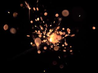 Sparkler on black background. Bokeh blur. Out of focus.