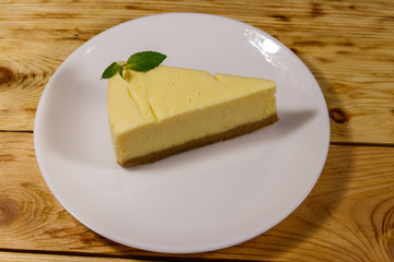 Piece of tasty sweet New York cheesecake in a white plate on wooden table