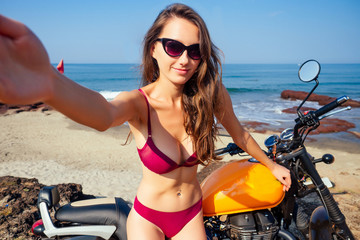 Sexy girl in a red bikini swimsuit sitting on a motorcycle royal enfield taking a selfie portrait on a smartphone on a background of tropical paradise sea and rock.travel and entertainment