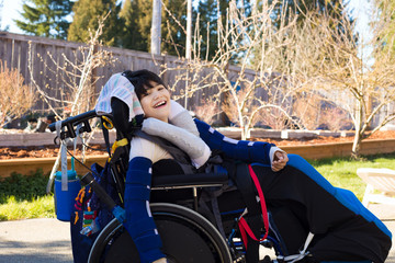 Happy boy in wheelchair outdoors smiling and laughing