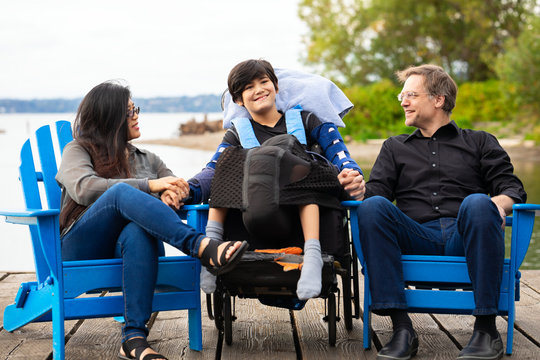 Multiracial couple with disabled boy in wheelchair outdoors by lake