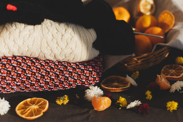 Tangerines, flowers, citrus in sraw basket, sweater warm, knitting  and orange slices. Christmas winter background, wallpaper or greeting card. Top view, flat lay, background, copy spaces.