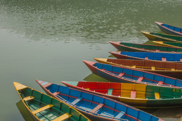 A lot of old wooden colorful boats on the water. blue red green and yellow boats on the lake