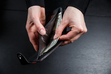 Hand in suit takes out dollar money from a wallet
