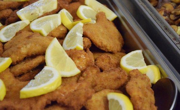 Panierte Schnitzel mit Zitronenscheiben auf einem Buffet