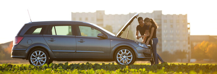 Young couple, handsome man and attractive woman at car with popped hood checking oil level in engine using dipstick on clear sky background. Transportation, vehicles problems and breakdowns concept.
