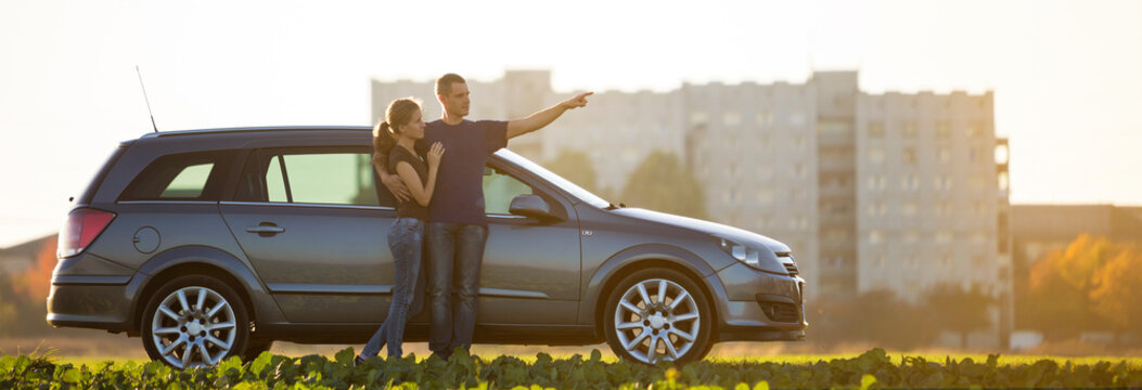 Young couple, slim attractive woman with long ponytail and handsome man pointing in distance standing at silver car in green field on blurred apartment building and clear sky copy space background.