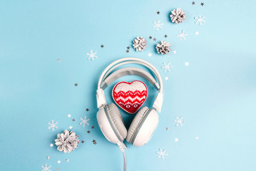 Headphones with winter heart, cones and snowflakes on blue background. Christmas music concept.
