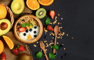 Granola and yogurt with fruits in wood bowl