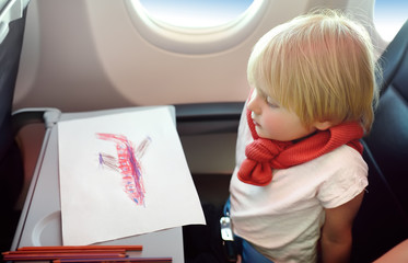 Joyful little boy sitting by aircraft window during the flight