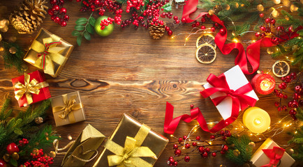 Christmas scene. Colorful wrapped gift boxes, beautiful Xmas and New Year backdrop with gift boxes, baubles, candles and lighting garland over wooden table background. Top view, flatlay