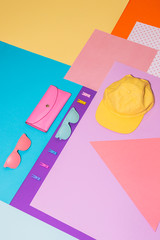 Flat lay fashion set with pink purse, colorful sunglasses and yellow cap on memphis style background. Geometry concept