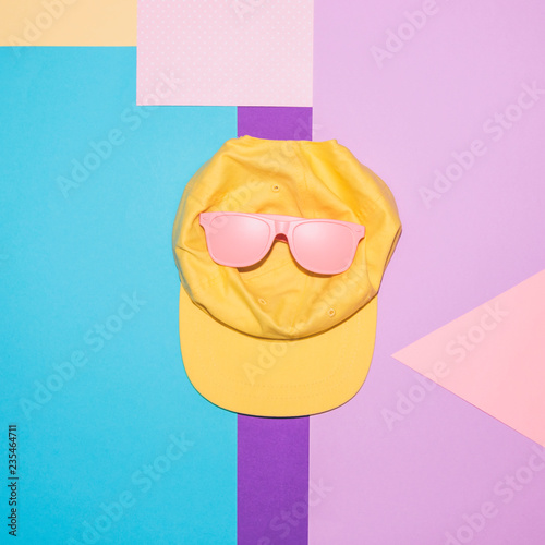 Pink sunglasses and yellow cap on colorful background