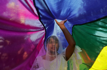 A participant touches a rainbow flag during Queer Pride March, an event promoting gay, lesbian, bisexual and transgender rights, in New Delhi