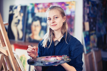 Young Woman Artist Working On Painting In Studio. Selective focus on foreground.
