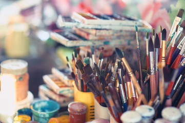 Paint brushes and watercolor paints on the table in a workshop, selective focus, close up. Wall mural