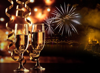 Photo sur Plexiglas Individuel two champagne glasses with ribbons against holiday lights and fireworks - New Year celebrations