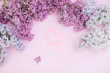 Lilac branches and two pink heart on a light pink background empty space for your text, top view. One big and one small heart like simbol of love