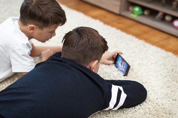 Little boys watching video by smartphone on carpet