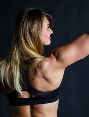 muscular female body long white hair against black background.