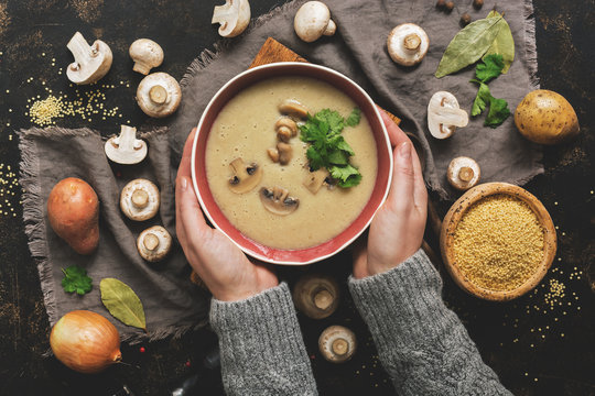 Women hands in a gray sweater holding a bowl of cream of mushroom soup. Hot winter soup on a dark rustic background. Top view, flat lay.