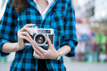 Young photographer taking vintage retro camera  on colorful background